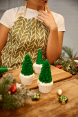 Cropped view of confectioner standing beside Christmas tree cupcakes and decorations on table