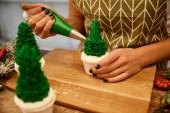 Vágott kilátás cukrászda hozzá édes krém karácsonyfa cupcakes fenyő ágak és karácsonyi labdák az asztalon