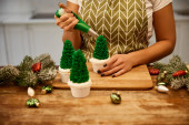 Cropped view of confectioner making Christmas tree cupcakes beside spruce branches and christmas decor on table