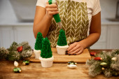 Cropped view of confectioner with pastry bag adding cream on Christmas tree cupcakes with pine branches on table