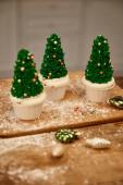 Ízletes karácsonyfa sütemények zöld krémmel és dekorációk vágódeszkán karácsonyi golyókkal