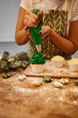 Cropped view of confectioner making cupcakes with green cream beside christmas decoration and pine branch on table