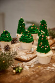 Decorated Christmas tree cupcakes with christmas balls with spruce branch and cones on table