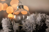 decorative transparent christmas ball on spruce branches in snow with blurred yellow lights