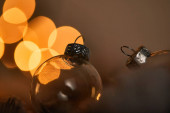 close up of transparent christmas balls with blurred yellow lights