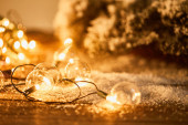 christmas garland with transparent light bulbs on wooden surface with spruce branches in snow
