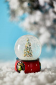 decorative christmas tree in snowball standing on blue with snow and spruce branches