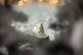selective focus of little snowball with christmas tree standing in snow with spruce branches and lights bokeh