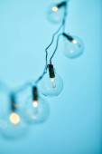 selective focus of christmas garland with transparent light bulbs isolated on blue