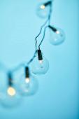 selektivní zaměření vánoční věnce s průhlednými žárovkami izolovanými na modré