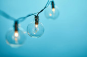close up of christmas garland with transparent light bulbs isolated on blue