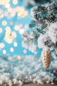Fotografie spruce branches in snow with christmas ball pine cone and blurred lights on blue