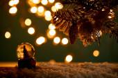 Fényképek kis hógolyó karácsonyfával áll a hóban lucfenyő ágakkal, karácsonyi labda és homályos fények éjszaka