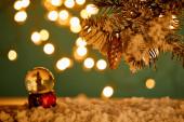 Schneeball mit Weihnachtsbaum im Schnee mit Fichtenzweigen, Weihnachtskugel und verwischten Lichtern in der Nacht
