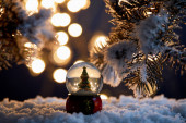 decorative christmas tree in snowball standing in snow with spruce branches and blurred lights at night