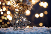 decorative snowflake with spruce branches in snow with christmas lights bokeh