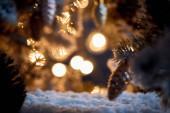 Nahaufnahme des Weihnachtsbaums mit dekorativen Weihnachtskugeln auf Schnee mit verschwommenem Licht im Dunkeln