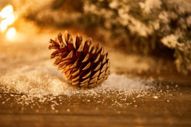 decorative pine cone on wooden table with spruce branches in snow and blurred christmas lights