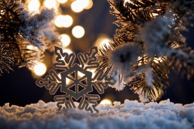 close up of decorative snowflake with spruce branches in snow with blurred christmas lights