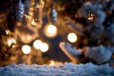 close up of spruce branches in snow with christmas balls and lights bokeh at night