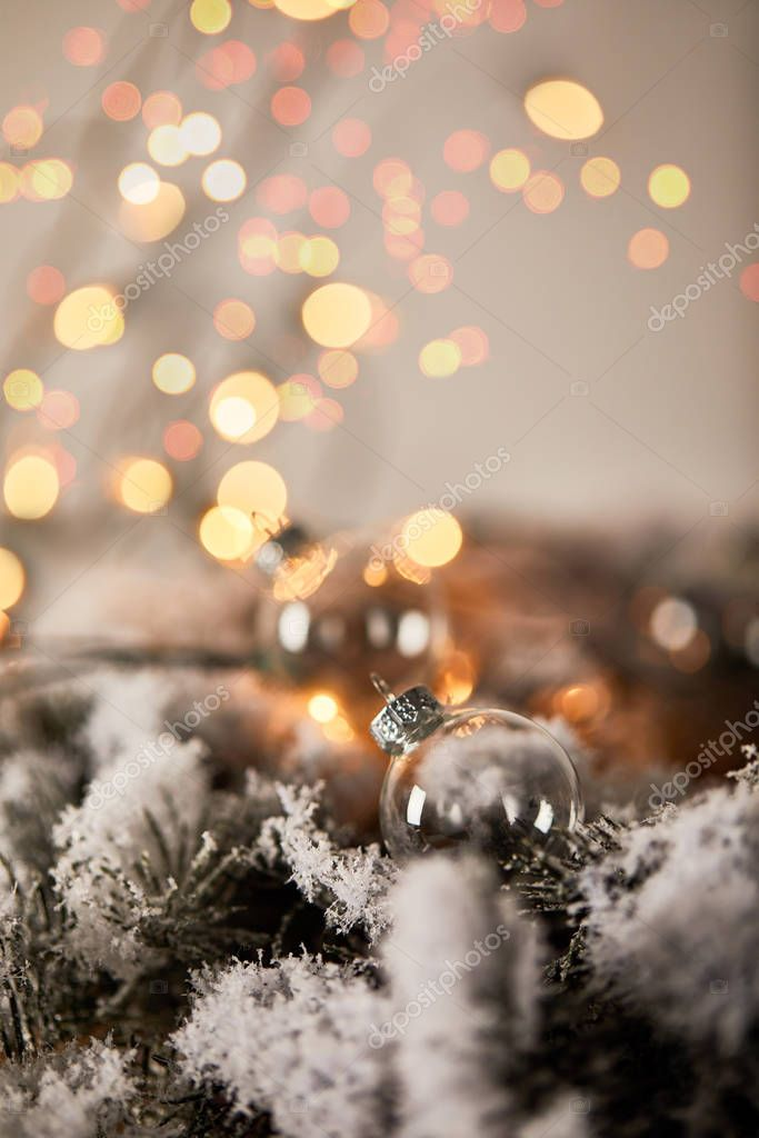 Transparent christmas balls on spruce branches in snow with blurred yellow lights