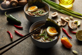 traditional spicy ramen in bowls with chopsticks and vegetables on stone surface