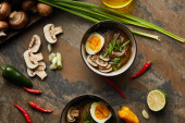 Photo top view of traditional spicy ramen in bowls near vegetables  and oil on stone surface