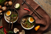 Photo top view of traditional spicy ramen in bowls with chopsticks and vegetables on brown napkin on stone surface