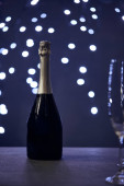selective focus of champagne bottle and glass with christmas lights bokeh