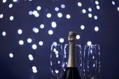láhev šumivého vína a sklenice s rozmazanými vánočními světly