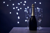 Flasche Champagner und Gläser mit verschwommener Weihnachtsbeleuchtung