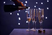 kivágott kilátás az ember öntő pezsgő poharak karácsonyi fények bokeh