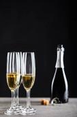glasses and bottle of sparkling wine on black