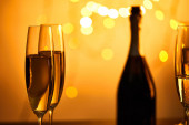 Fotografie glasses of sparkling wine with blurred bottle and yellow christmas lights