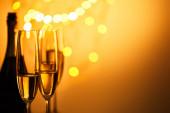 sklenice a láhev šumivého vína se žlutými vánočními světly bokeh