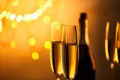 sklenice šumivého vína s rozmazanou lahví a žlutými vánočními světly