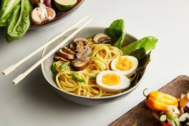 Traditional asian ramen in bowl near chopsticks, vegetables on grey surface stock vector