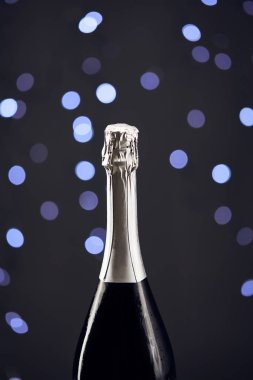 Close up of sparkling wine bottle with blue christmas lights bokeh stock vector