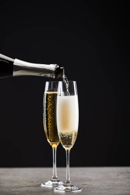sparkling wine pouring from bottle into glasses for celebrating christmas on black