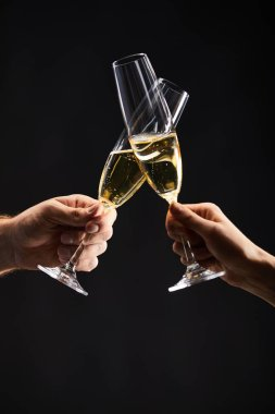 cropped view of man and woman clinking with champagne glasses and celebrating christmas, isolated on black