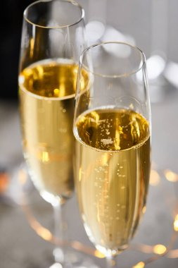 Close up of glasses of sparkling wine with blurred yellow christmas lights stock vector