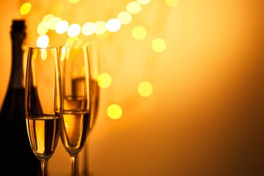 Glasses and bottle of sparkling wine with yellow christmas lights bokeh stock vector