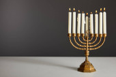 burning candles in menorah isolated on grey