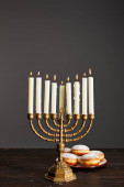 delicious doughnuts near burning candles in menorah on wooden table on Hanukkah isolated on grey