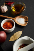 Spices, chili peppers with salt on wooden spoon and olive oil on black wooden background