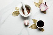 Top view of peppercorns, soy sauce with onion and garlic on bay leaves on marble background