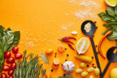 Top view of fresh vegetables, herbs with spices on orange background