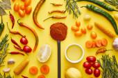 Fotografie Horní pohled na organickou zeleninu a bylinky s chilli kořením na žlutém pozadí