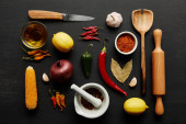 Top view of kitchenware with organic vegetables and spices on black wooden background