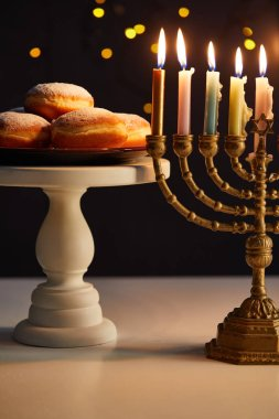 Delicious doughnuts on stand near glowing candles in menorah on black background with bokeh lights on Hanukkah stock vector